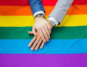 Regenbogenflagge mit zwei Männerhänden
